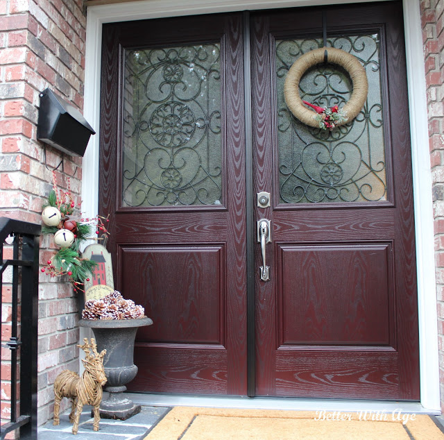 Reddish front door with holiday wreath, a planter filled with pine cones, and twine reindeer.