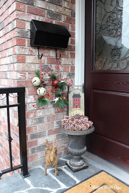 Black mailbox with jingle bells hanging off of it, pinecones in planter and twine reindeer on porch.