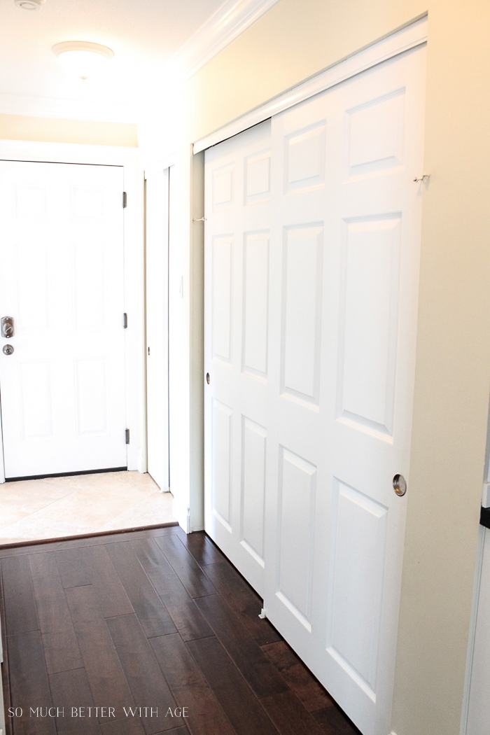 A hallway with wooden floors and white doors.