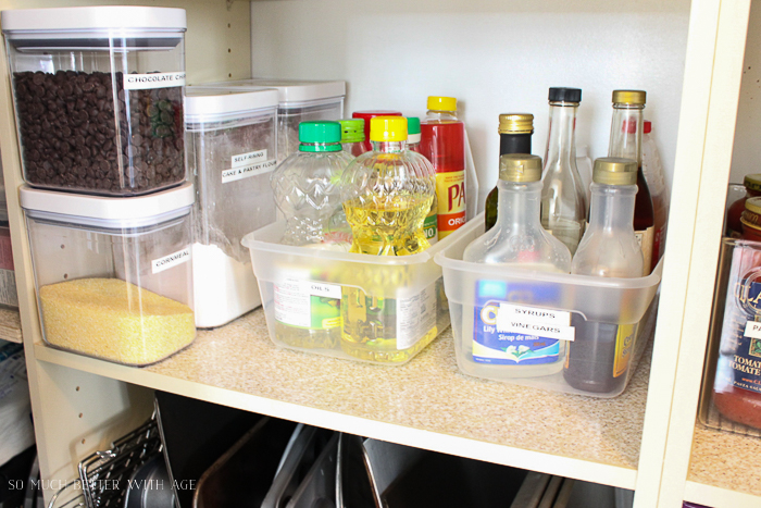 Oil, syrup and chocolate chips in containers in the pantry.