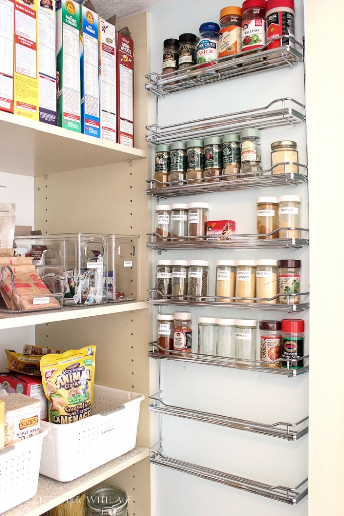 A spice rack on the back of the door with wire shelves of racks of spices.