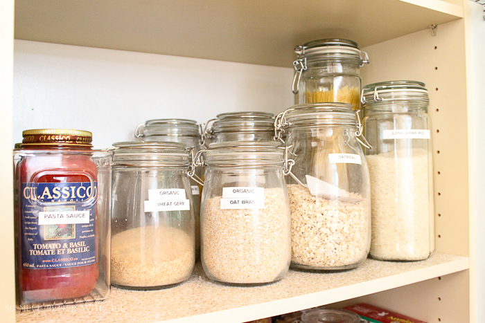 Clear glass jars with sugar and flour and pasta sauce on the shelf.