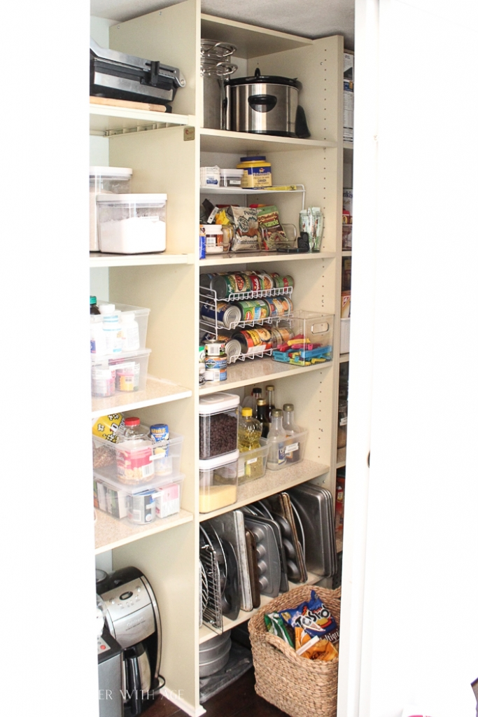 Side view of the pantry shelves with the baking sheets on the bottom organized.