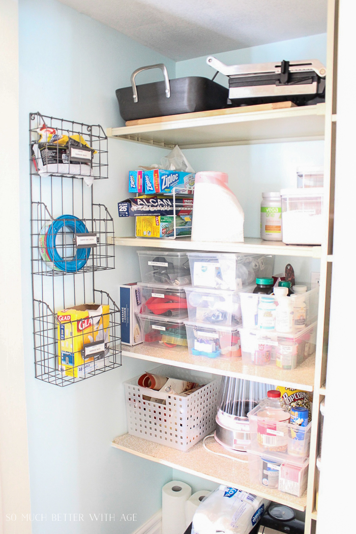 A pantry with wooden shelves and a wire rack.