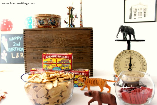 Animal crackers in bowl with circus animal figurines on table.