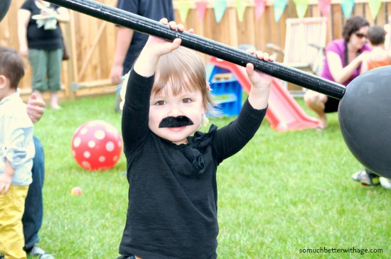 Little girl with a moustache holding a barbell.