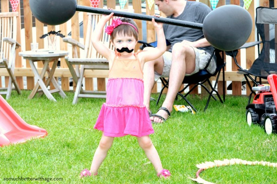Little girl in a pink dress holding a barbell.
