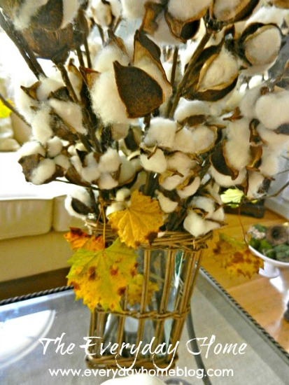 Yellow leaves with cotton in a twig vase on a coffee table.