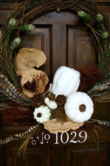 Dark brown front door with wreath hanging on it.