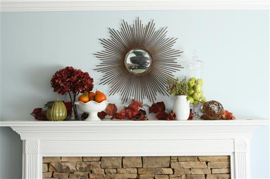 White mantel decorated with orange and red leaves for fall.