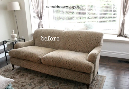 A neutral patterned couch on a rug.