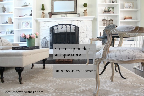 Faux peonies in a green sap bucket.