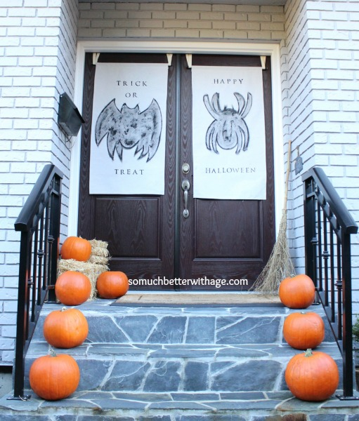 Front porch with pumpkins on stairs leading up to front doors with bat and spider posters on them.