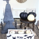 Glittery black pumpkins on side table.