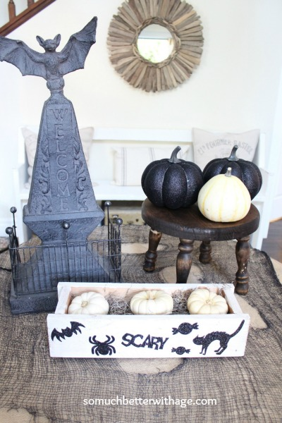 Glittery black pumpkins on side table.