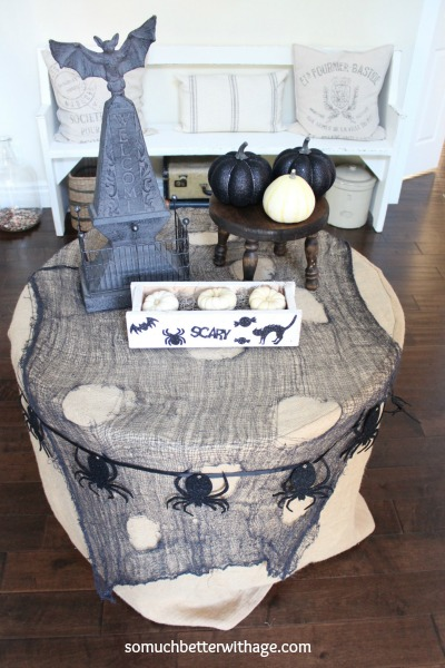 Side table in foyer decorated with black cloth and black pumpkins and scary bats.