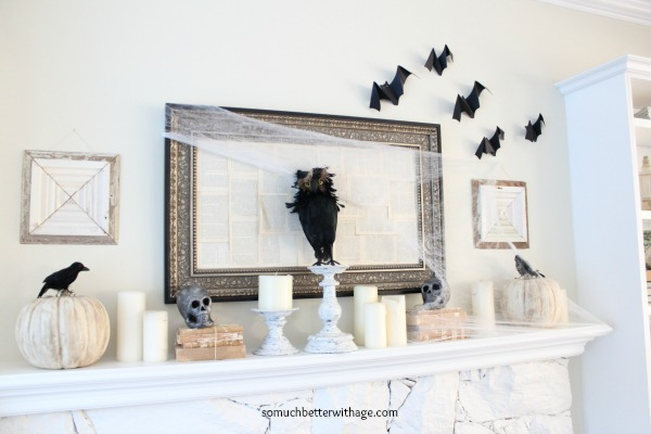 Black bats on wall and pumpkins on white mantel.