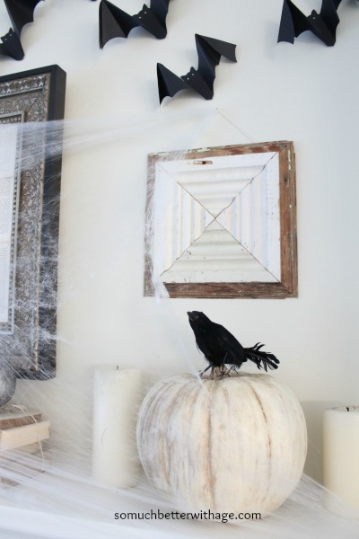 Black crow sitting on a pumpkin on the mantel display.