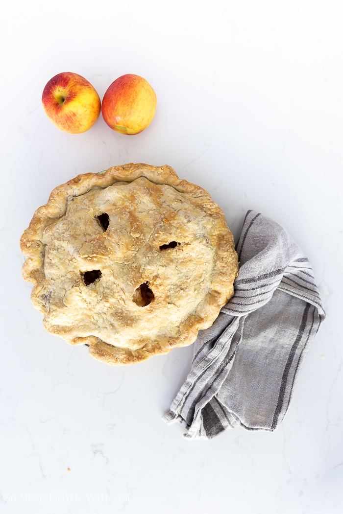 Apple pie on counter with two apples.