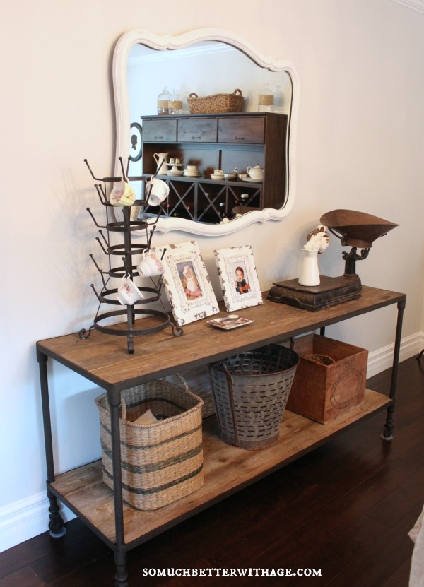 Restoration hardware console table with wicker baskets on it.