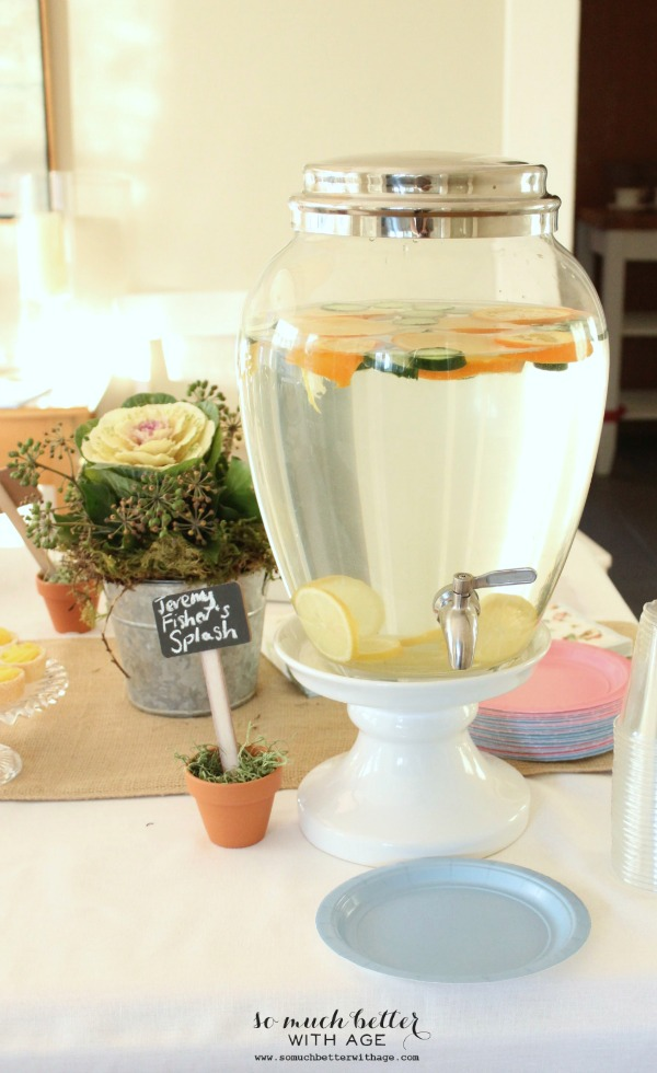 A water jug with a spout with cucumber and orange and lemon in it.