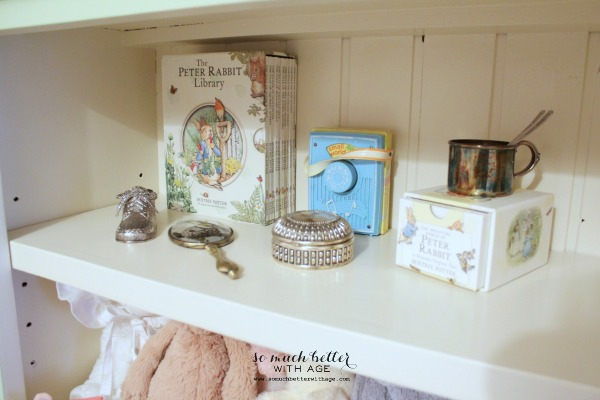 Peter Rabbit Library books on the shelf, with baby keepsake items.