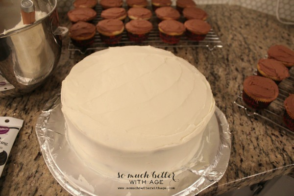How to ice and decorate a cake like a pro / cake on counter with cupcakes - So Much Better With Age