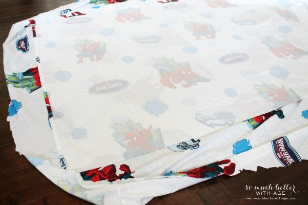 The Superman tablecloth with the bottom fitted part cut out on the floor.