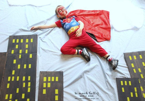 Little boy dressed as Superman lying across the backdrop.