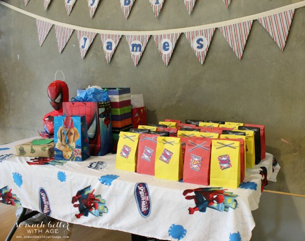 Superhero themed table with party bags and banner.