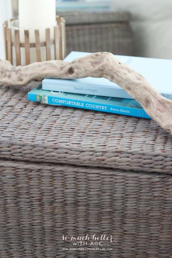 Up close of the grey wicker basket with a piece of driftwood on it and books.