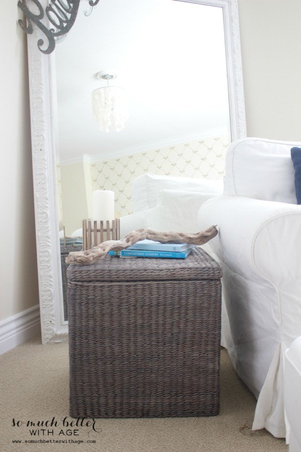 The grey wicker basket in front of a large white mirror.
