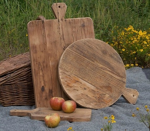 Wooden cutting boards outside by the grass on a blanket.