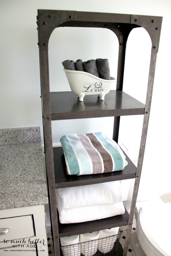 Industrial metal shelving unite with towels on it.