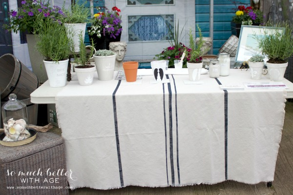 White tablecloth with blue striping down the middle on a table outside.
