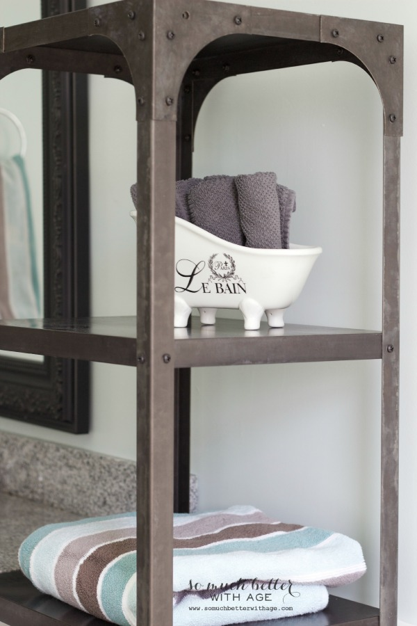 Bathroom steel shelf with pottery on it and towels.