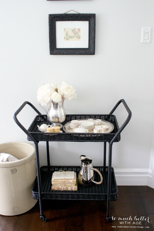 Dark wicker serving cart with a pitcher, cookies, plates and flowers.