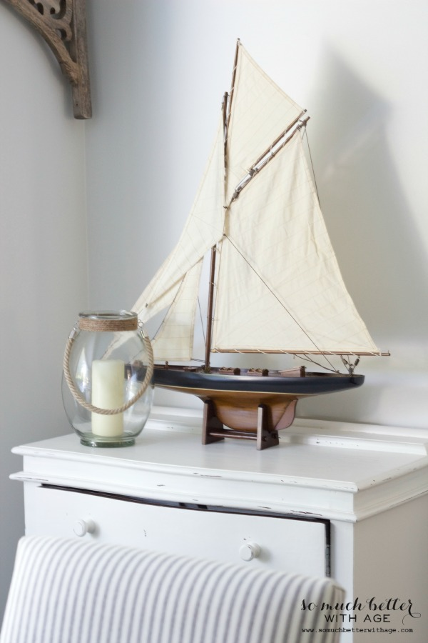 Wooden model sailboat with white fabric sails on side table.