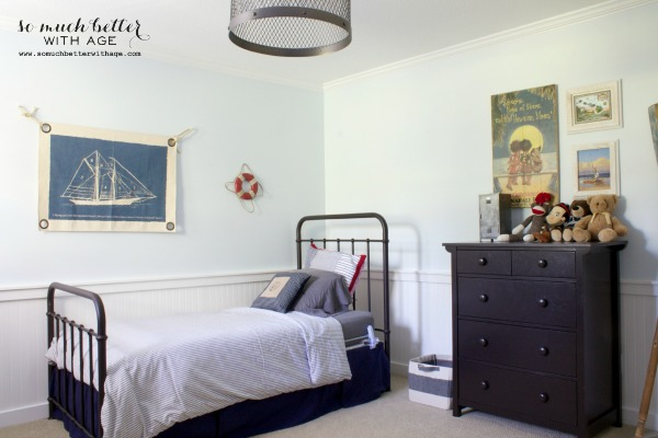 A wrought iron bed, a sailboat picture on the wall and a dark brown dresser in bedroom.