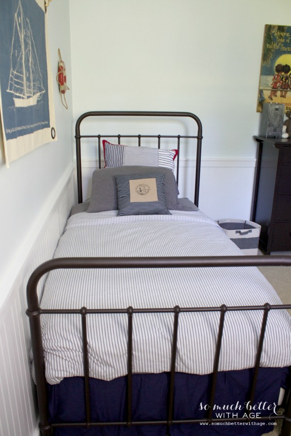 Metal single bed frame with gray pillows and a striped comforter on bed.