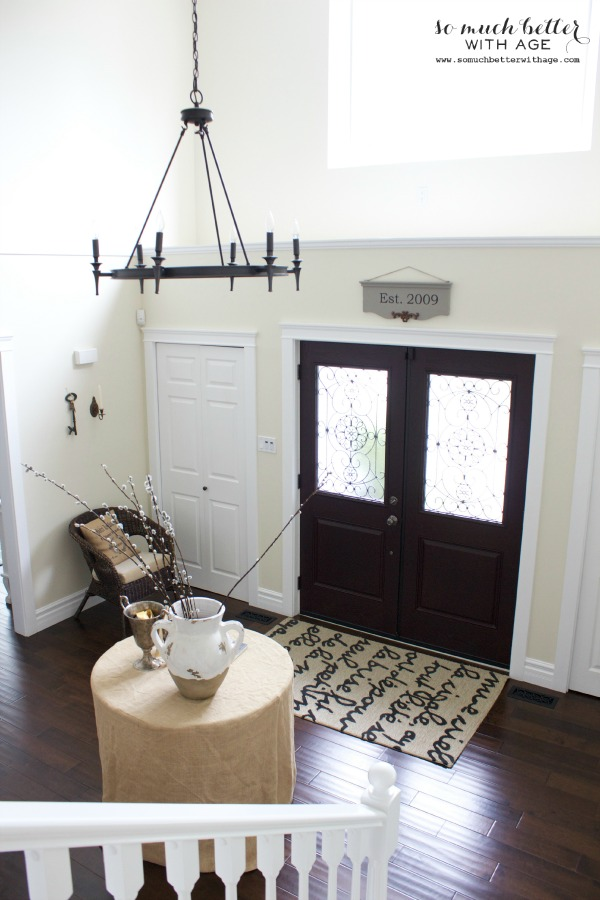 Foyer with rug and table and chandelier.