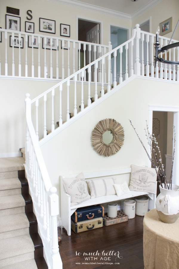 Neutral foyer with stairs leading up and bench on the bottom of the stairs.