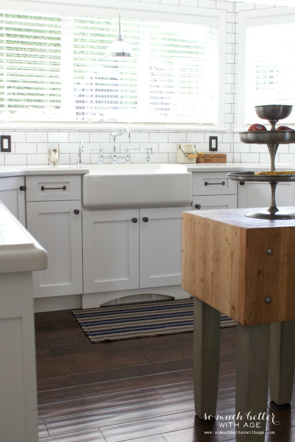 White kitchen with wooden island.
