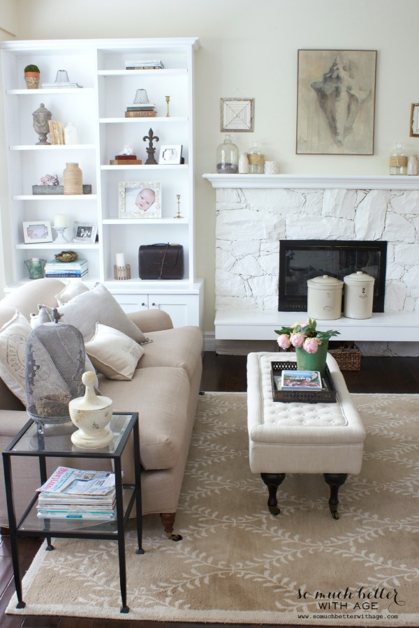 Neutral coloured couch in the living room with the white fireplace and crocks on the mantel.