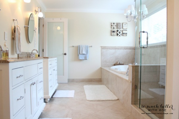 Large master bathroom with white cabinets and tub and shower.