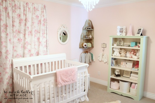Girl's nursery with pink walls and flowery curtains.