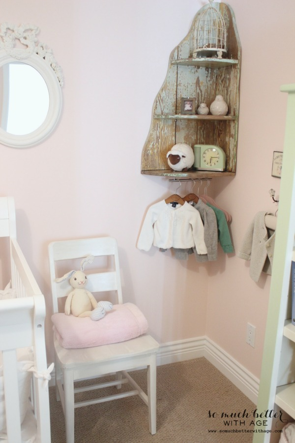 Little girl's clothes hanging from wooden shelf in corner.