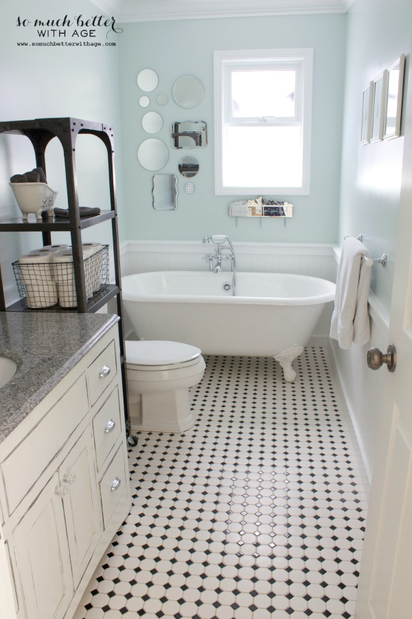 The powder room with a black and white checked floor and white claw foot tub.
