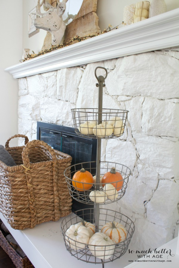 Wire baskets filled with pumpkins on the fireplace mantel.