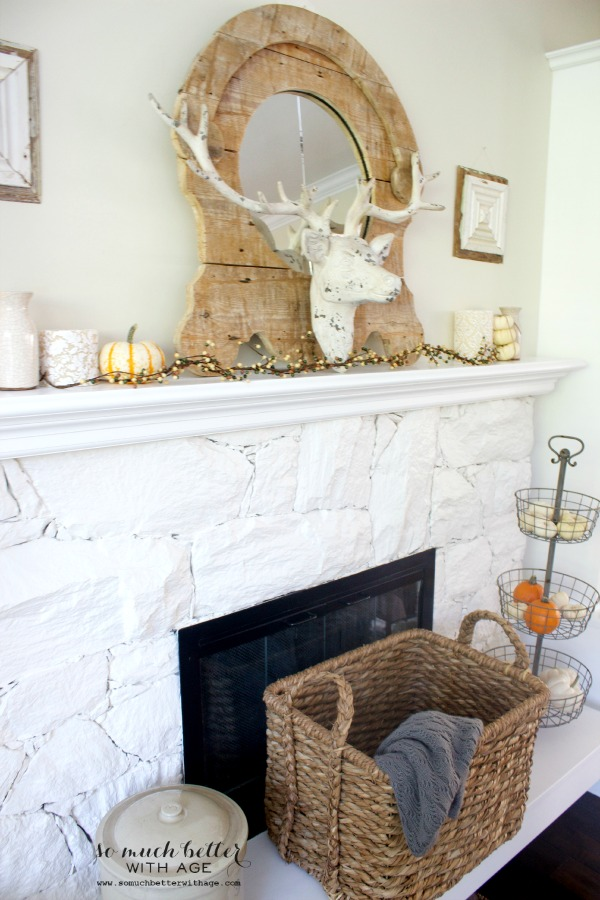 Antlers on the mantel with pumpkins and a wooden mirror.